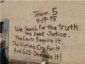 A woman, at the left of the image, is reading a black spray paint message written on a brick wall. The message reads