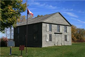 Exterior view of the Old Hay Bay Church with Canada flag and plaque out front