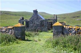A grass-covered driveway leads between two stone pillars with orange lichen on their pyramid-shaped tops. Beyond is a stone building with ruined outhouses and green hills with a blue sky in the background