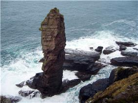 A tall sea stack consisting of a layered sedimentary rock  is situated off a rocky coast and sits amid breaking waves and foamy waters.