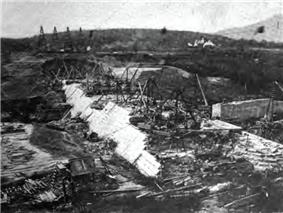 A black and white photograph of the lower sections of a sloped dam, with cranes and other construction equipment on top