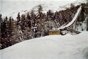 A snow-covered ski jump with the words,