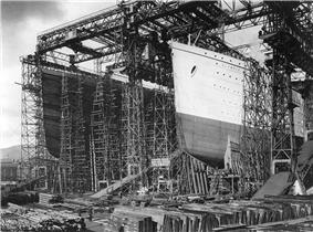 Photograph of a huge gantry with two openings in it, one of which is filled with the bows of a large ship that has been painted in light and dark colours.