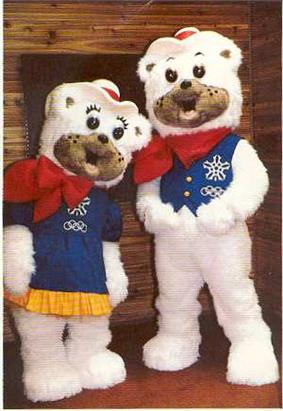 Two polar bear mascots with fuzzy white fur. The female is wearing a blue dress, the male a blue vest. They each wear a red bandana and cowboy hat.