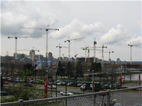 At least a dozen cranes rise over buildings under construction. In the foreground, cars are driving by on existing streets, and a city skyline rises in the background.