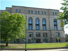 A beige five-story municipal building with large, arched windows. A tree is in front of the building.