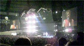 Brightly lit stage, with large screens and a big crowd