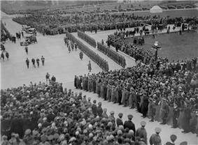 Black and white photo: Crowds of people and a ranked military guard gather to watch four men in ceremonial uniform approach a set of stone steps.