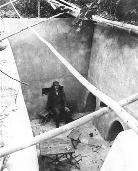 A soldier sitting on a chair in a large exposed underground room. To the right are two large holes in the wall while the room is littered with other furniture, including a makeshift table.