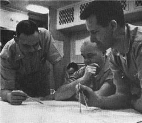 Three naval officer plotting the submerged course of the nuclear submarine Triton, with Captain Beach seated before chart in the center, with Lt. Commander Will M. Adams standing at right holding a pair of dividers and Lt. Commander Robert W. Bulmer standign at the left holding a pencil, and an unidentified individual seated in the background.