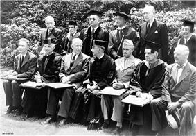 Thirteen men pose for a formal picture. Seven are sitting and six standing. There are all wearing either suits or academic gowns, except Bradley, who is in his Army uniform with a garrison cap.