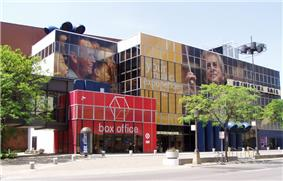 Modern building, red entrance labeled BOX OFFICE, in front of yellow and blue segments. Trees planted in front. Advertising has images of people's heads painted on building.