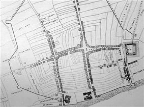 A black and white map, showing a town with a central street, criss-crossed by two adjoining small roads and a small castle on the far right of the map.