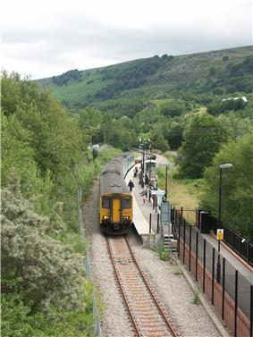 Aerial view of four carriage train, on single curved track, at station. Passengers wait to board. Lush wooded mountains make up the background on all sides. To the right, foreground, a walkway leads down to the platform.