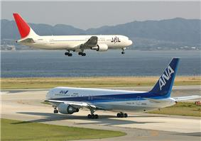 A white and red-tailed Japan Airlines aircraft above runway, with landing gears down, and an All Nippon Airways in blue and white livery taxiing.