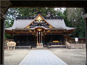 Wooden building with a large roof and central gable on the front. Both the roof and the lower part are in very dark colors. Three ropes are hanging down from the front centre gable.