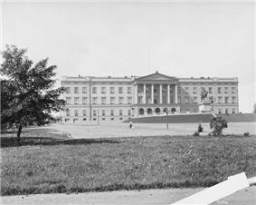 Massive, rectangular, three storied, granite palace with a flat roof; front pediment has six large columns. A large staircase leads to area with balustrades and to the front entrance with five rounded arches.