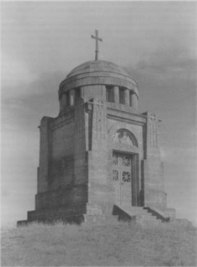 The Ostrach battle monument is a small, square building, raised from the ground about .5 meter, 8 meters high. A 3 meter dome, topped with a simple cross, caps the monument. It is of marble, with a simple double door.