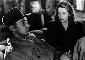 Black-and-white image of a man and a woman sitting side by side on a couch, viewed at an angle. The man, in profile in the left foreground, stares off to the right of frame. He wears a trenchcoat, and his face is shadowed by a fedora. He holds a cigarette in his left hand. The woman, to the right and rear, stares at him. She wears a dark dress and lipstick of a deeply saturated hue.