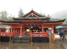 Frontal view of a wooden building with vermillion red beams. A platform with red handrail is located in front of the building.