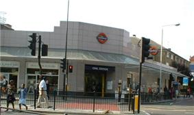 A grey-tiled building with a rectangular, dark blue sign reading