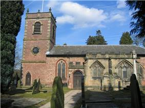 A church with a brick Neoclassical tower and body and a stone Gothic chapel protruding in the foreground