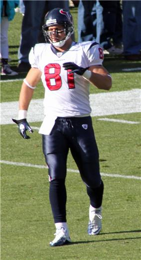 A light-skinned man wearing a white football jersey and dark blue pants