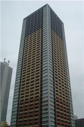 Ground-level view of a rectangular, window-dotted high-rise; the facades are tri-colored with white, beige and gray areas