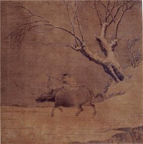 A boy riding an ox and a tree.