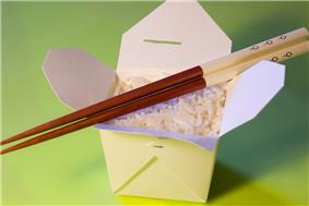 A plain oyster pail, lid opened, without a wire handle, containing plain white rice with a pair of chopsticks laid across the top