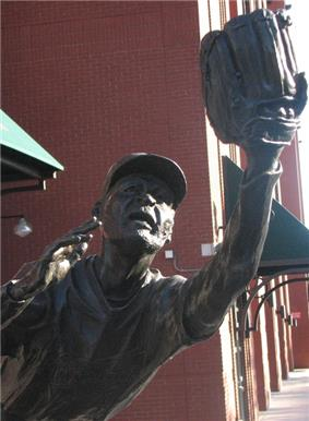 A bronze statue in the likeness of Ozzie Smith, depicting him fielding a baseball