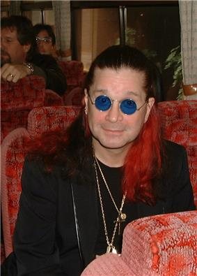 A man with red coloring on his dark hair, wearing sunglasses, necklaces, and a black suit. He is seated on a red chair, and two people are also seated in the background.