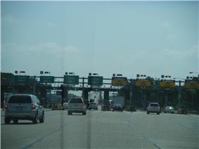 Multi-lane toll plaza before bridge: half cash and half E-ZPass lanes