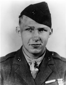 Head of a young man in military uniform with a quizzical look on his face. His garrison cap is tilted off to one side and a tuft of short hair sticks out from the other.