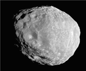 An irregular body, whose outline looks like an approximate circle in this image. It is illuminated from the bottom-left. The terminator runs from the top-left to bottom-right. The surface is covered by craters.