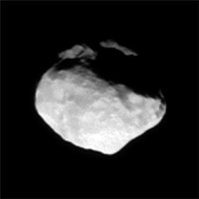 An irregularly shaped body illuminated from the left. Its surface is covered by numerous impact craters.