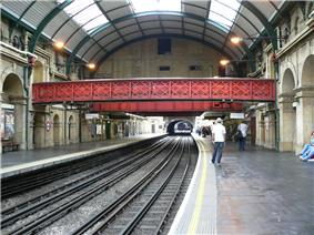 The interior of a building with a rounded ceiling and a railway track running down the middle of the corridor flanked by brick arches