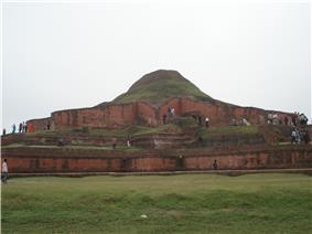 Ruins of a structure of red stone now resembling a small hill or mound.