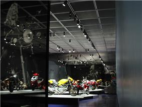 Translucent panel reaching floor to ceiling, with image of voluptuous blond woman on a motorcycle in front of chamber with several motorcycles on pedestals.