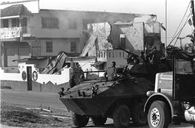photograph of a Marine LAV-25 and utility truck in the foreground with a partially destroyed building in the background