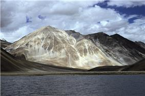 Daytime view of a large body of water standing before a prominent peak, which communicates with several others partly out of view and behind. A gravel beach at the far end of the lake gives way to steep slopes leading up to the peaks; The mountains lack trees. Patchy snowcover defines their recesses, and whitish vein-like streaks extend up from the base of the largest.