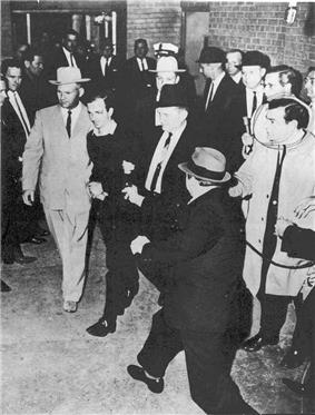A black-and-white photograph showing a man with men on either side of him walking past people on either side, from above. At the bottom right a man with a hat has a gun pointed at the man in the center.