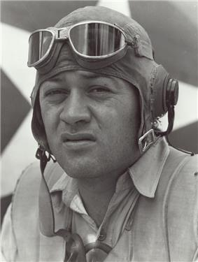 Head of a squinting man wearing a shirt unbuttoned at the collar and a cloth aviator's cap with headphones built into the ear flaps, an unbuckled chin strap, and goggles pushed up onto his forehead.