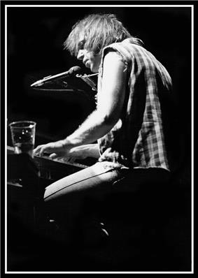 Black-and-white photo of a man playing the piano, there is a dink on the piano.