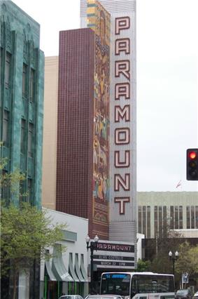 Photograph of a tall sign and mosaic announcing the Paramount Theatre standing above the marquee and a busy street.