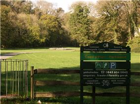 Cairn in the distance in sunshine, with trees in leaf to its left, right and rear. To its front lies flat ground of short grass. An asphalt path leads from the left past the tumulus. The shaded foreground has a kissing gate, a wooden fence and a Forestry Commission welcome sign in Welsh (first) and English.
