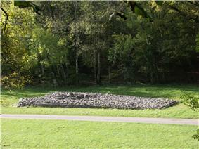 Elevated view of the cairn in the middle distance, from its side, with deciduous trees in leaf to its rear. To its front passes a wide asphalt path, dissecting flat ground of short grass. The tumulus' trapezium shape is evident, its boulders retained by a short wall, missing at the very front, left, where the rubble has tumbled out.