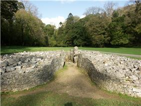 Front view of cairn, its boulders retained by a short, coursed, dry-stone wall that forms a bell-shaped courtyard at its entrance. The cromlech is set in flat ground of short grass. Trees are mainly in leaf to its rear.