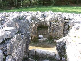 Internal view of cairn. A rectangular transept chamber is shown, with limestone orthostats and the remains of a sill at its entrance from a passageway. Boulders are piled up to its left, right and rear. The image has been taken from the chamber's pair, on the other side of the passageway.