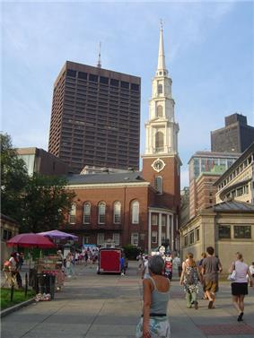 Ground-level view of a brick church with a large, white, tapering spire; a brown skyscraper is visible in the distance, with several shorter high-rises located closer to the church.